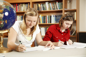 Two female students work on school work in a library